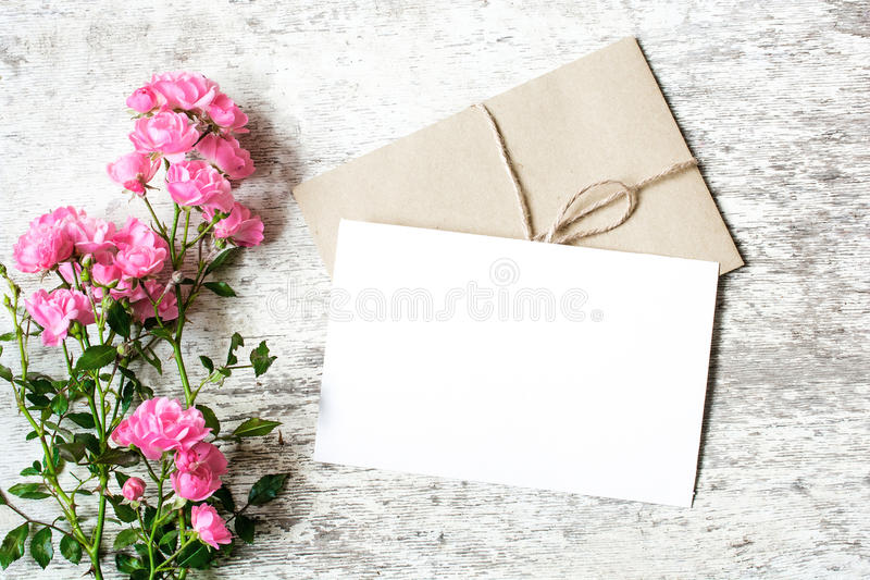 Blank white greeting card and envelope with pink rose flowers. Mockup on white rustic wood background for creative work design. top view stock photo