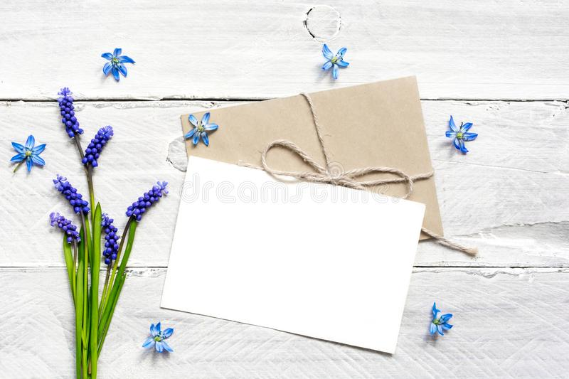 Blank white greeting card and envelope with spring blue flowers bouquet and buds stock image