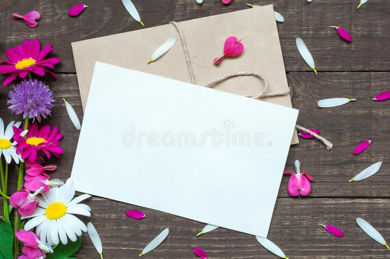 Blank white greeting card and envelope with wildflowers bouquet and buds with petals around royalty free stock photo