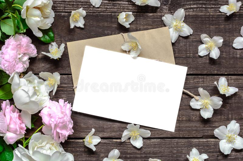 Blank white greeting card in frame made of pink roses and white jasmine flowers and envelope on rustic wooden background stock photo