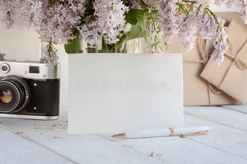 Blank white greeting card with lilac flowers bouquet and envelope with vintage camera on white wooden background. mock up royalty free stock image