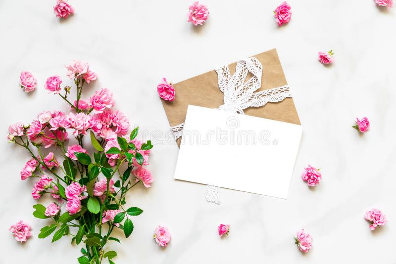 Blank white greeting card with pink rose flowers in frame made of flower buds on white marble background. mock up royalty free stock images