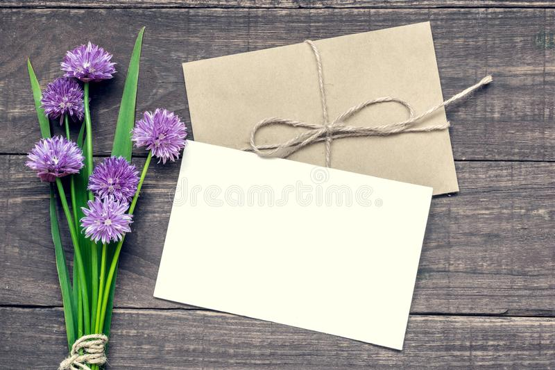 Blank white greeting card with purple wildflowers bouquet and envelope over rustic wooden background royalty free stock photography