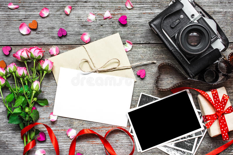Blank white greeting card with retro camera, blank photo, gift box and pink roses royalty free stock images