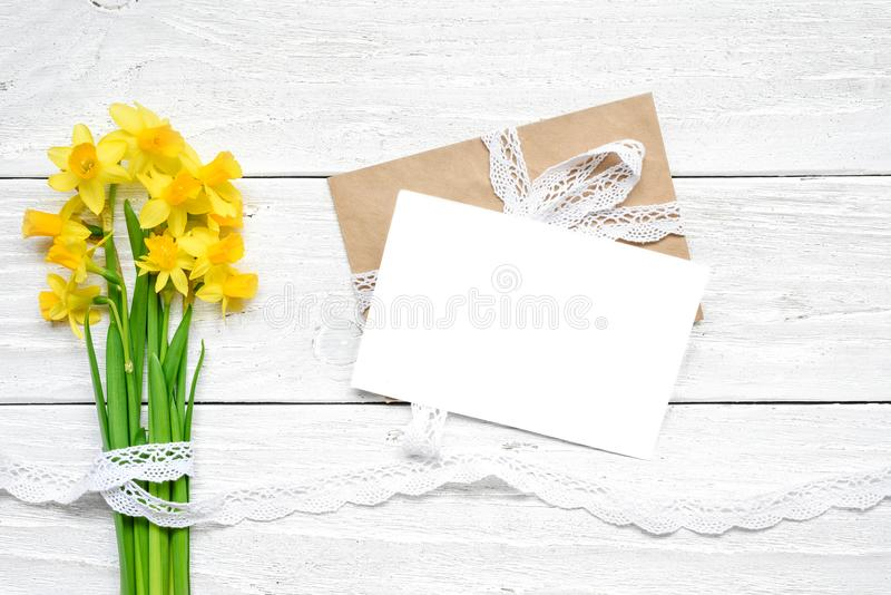 Blank white greeting card with spring yellow narcissus flowers bouquet over white wooden table. mock up. royalty free stock images