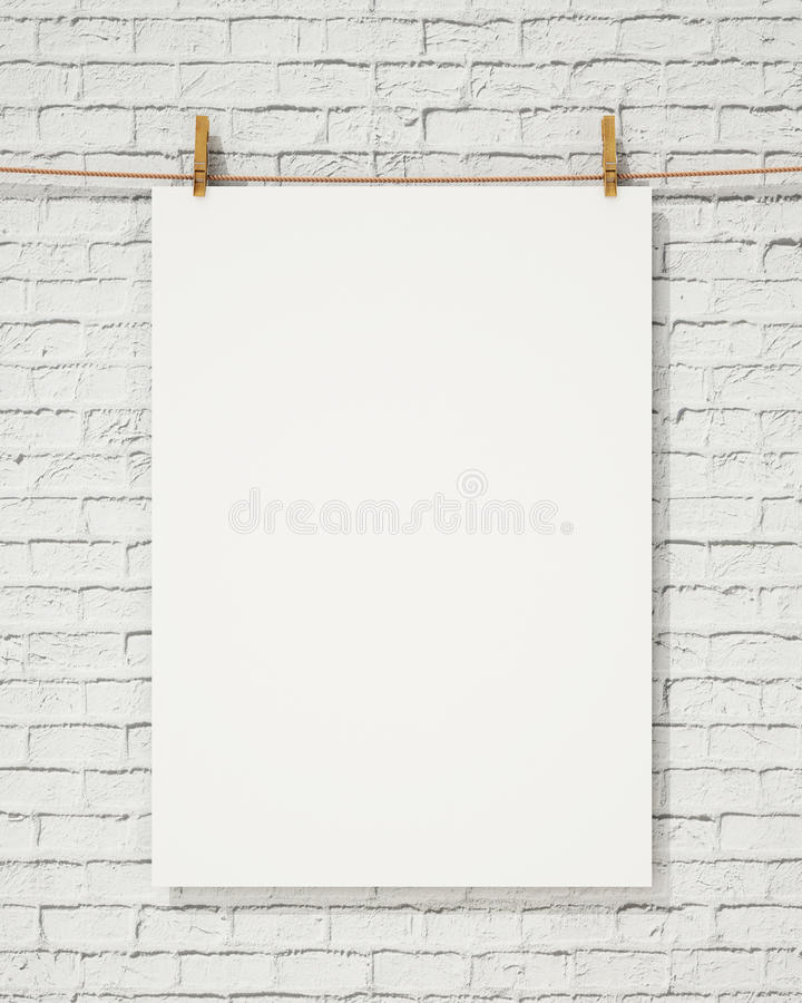 Blank white hanging poster with clothespin and rope on brick wall, background. Mock up design stock image