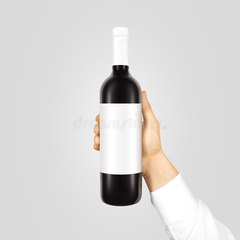 Blank white label mock up on black bottle red wine. Blank white label mock up on black bottle of red wine in hand isolated. Alcohol bottle mockup presentation stock photography