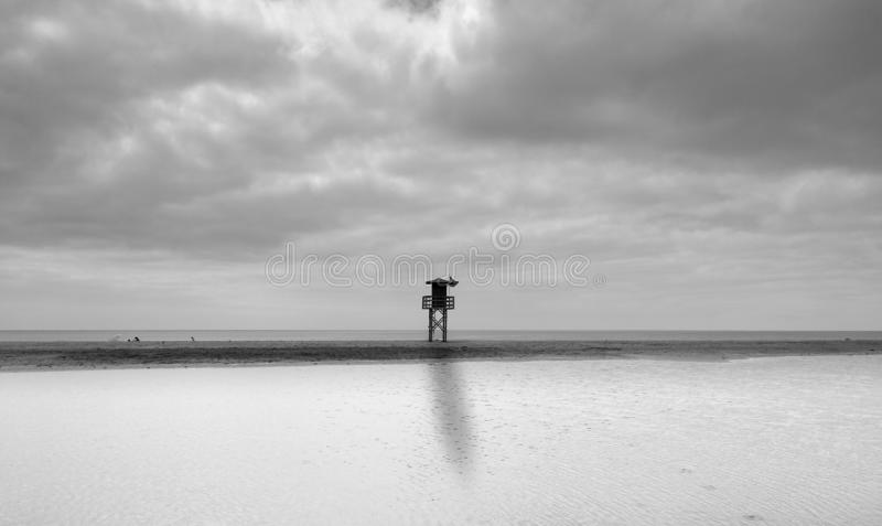 Blank and white landscape of a beach with cloudy sky,a tall lifeguard station with green flag at the middle. At first sea water. Has entered in the beach sand royalty free stock photography