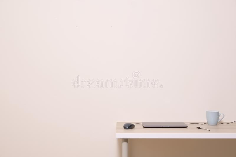 Blank white advertisement wall above office home desk cup laptop mouse pen neutral empty background. Blank white message advertisement wall above office home stock images