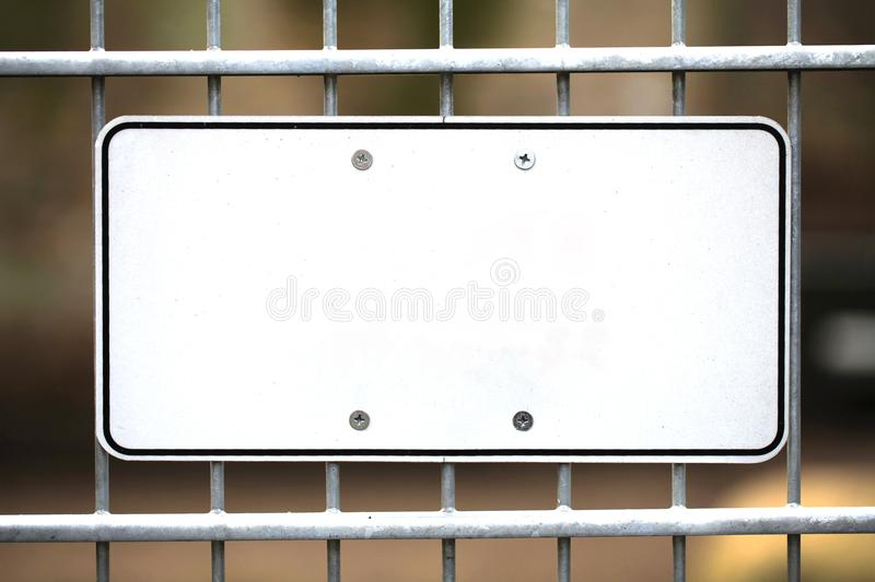 Blank white metal sign mounted to a fence. A blank white metal sign mounted to a fence royalty free stock photo