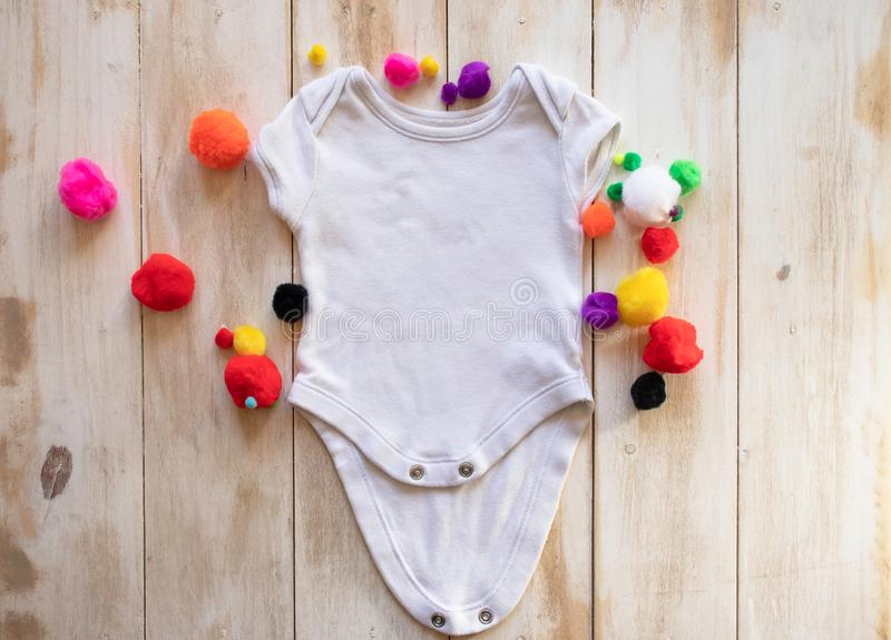 Blank, white mock up baby bodysuit shirt on a light white-washed wooden background surrounded by multi-coloured craft pom poms royalty free stock image