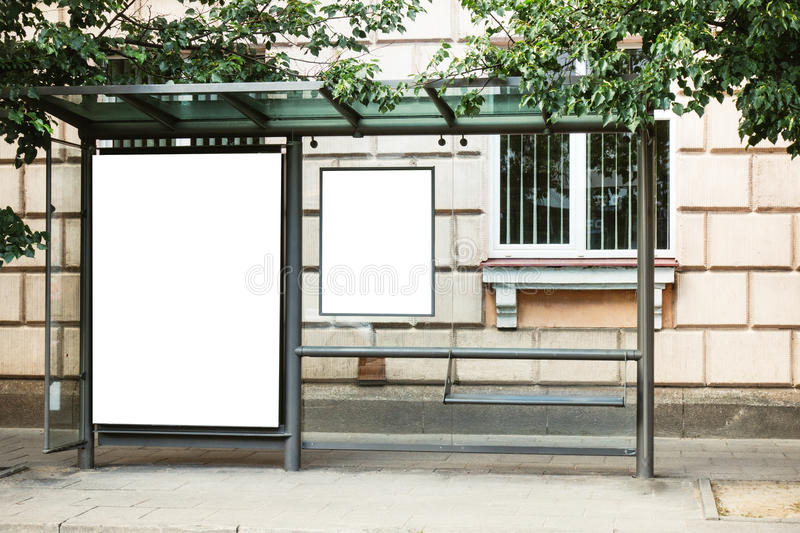 Blank white mock up of bus stop vertical billboard in front of empty street background royalty free stock photography