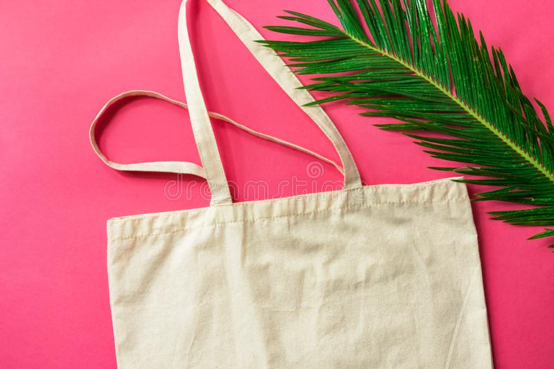 Blank white mockup linen cotton tote bag green palm leaf on fuchsia pink background. Zero waste reusable nature friendly materials stock photo