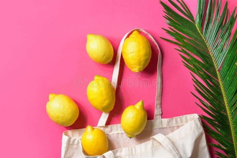 Blank white mockup linen cotton tote bag organic lemons green palm leaf on fuchsia pink background. Zero waste reusable materials royalty free stock photo