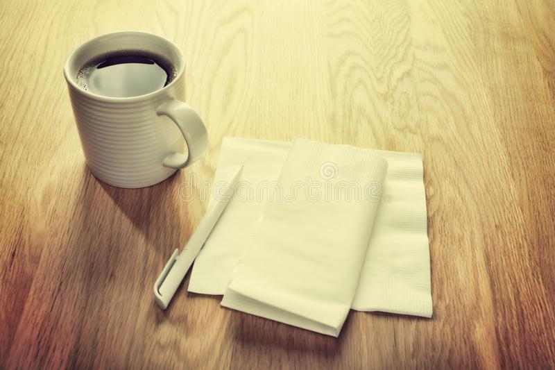 Blank White Napkin or Serviette and Pen and Coffee. Instagram effect - white napkin or serviette and pen on oak surface, ideal for notes and phone numbers, and royalty free stock image