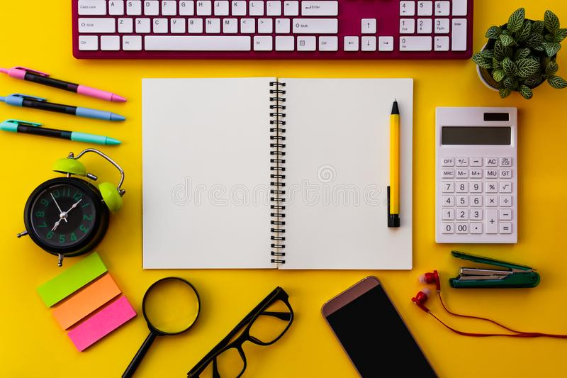 Blank white notepad with office and personal accessories isolated on yellow background royalty free stock photos