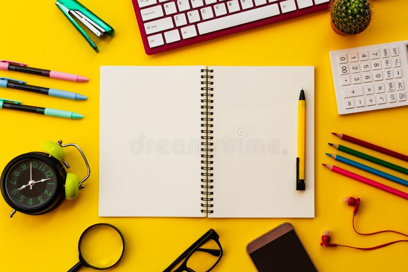 Blank white notepad with office and personal accessories isolated on yellow background stock photo