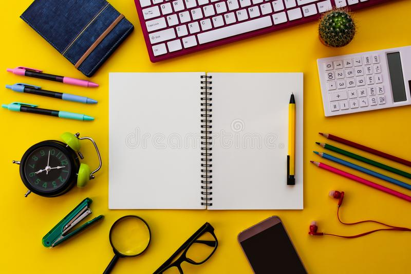 Blank white notepad with office and personal accessories isolated on yellow background royalty free stock photo