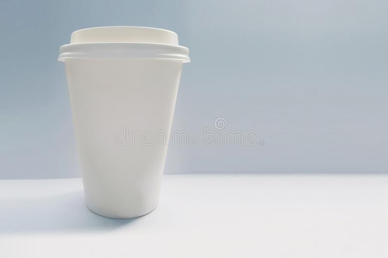 Blank white paper coffee cup mockup  isolated on a light background. Single-use disposable cup with no branding stock photo