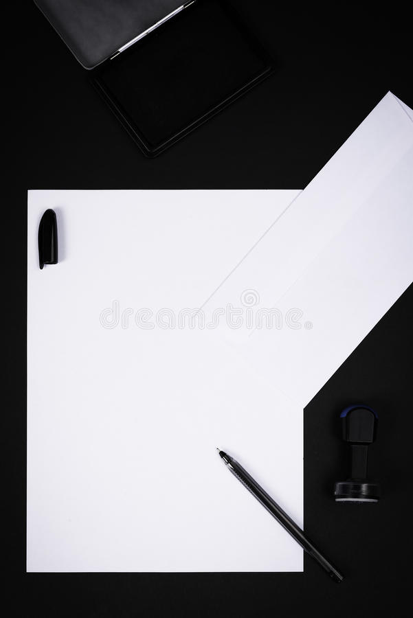 Blank white paper with letter, stamp, pencil and ink pad. On black background stock image