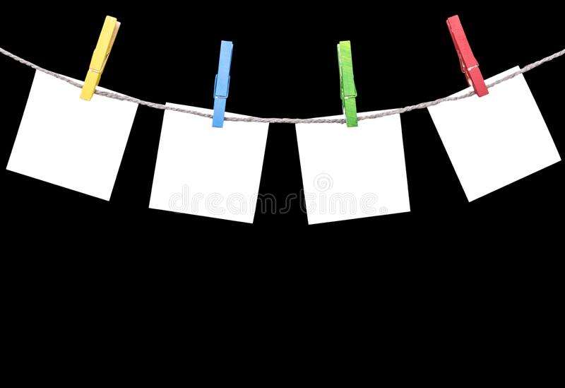 Blank white paper lists pinned with clothespins on rope isolated on black background. Blank white paper cards hanging with clothes. Pins with rope on black royalty free stock image