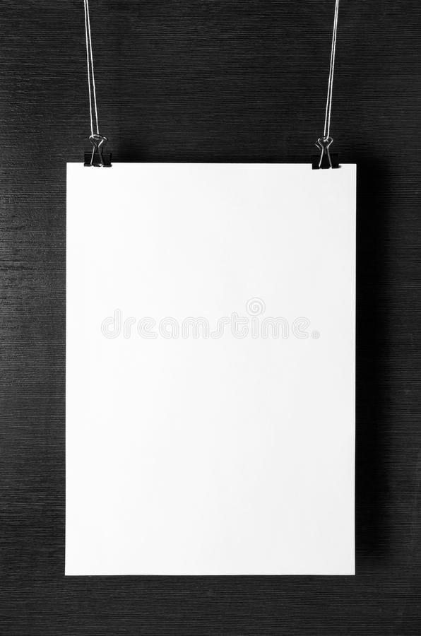 Blank white paper poster. Hanging on dark background. For design presentations and portfolios. Front view stock photos