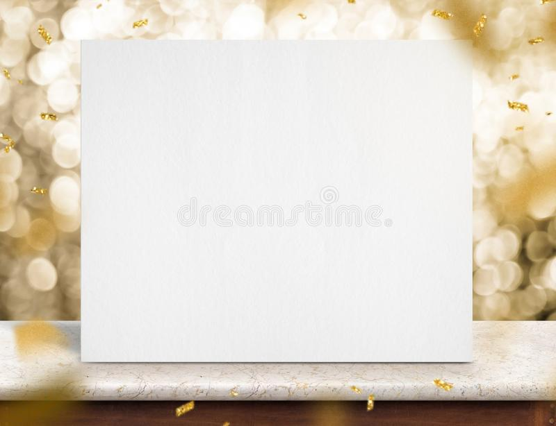 Blank white paper poster on marble table with gold sparkling con stock photo