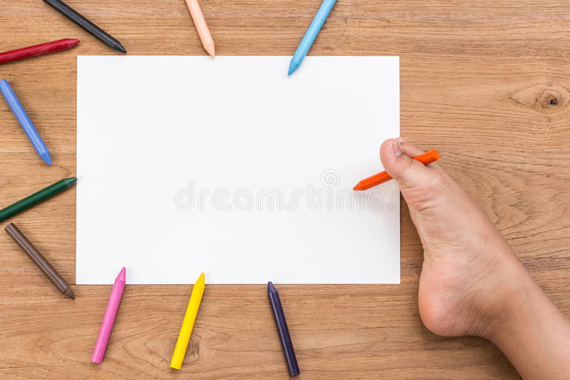 Blank of white paper and right foot of disabled people with pen. Blank of white paper and right foot of disabled people with color crayon on wooden desk. Use for royalty free stock photos