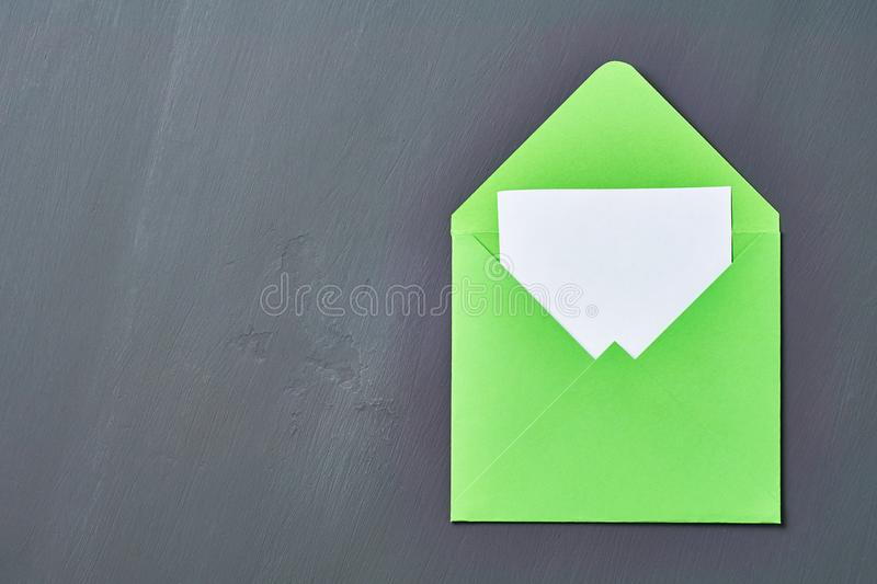 Blank white paper sheet in green opened square envelope lies on old scratched dark concrete. Space for text. Top view stock images