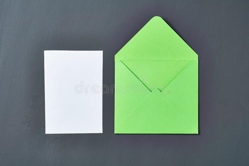 Blank white paper sheet near green opened square envelope lies on old scratched dark concrete. Space for text. Top view royalty free stock photography