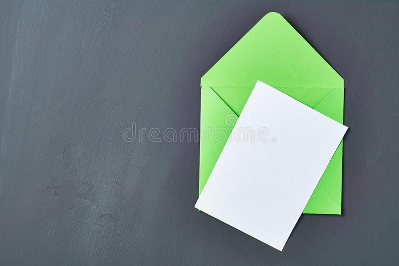Blank white paper sheet near green opened square envelope lies on old scratched dark concrete. Space for text. Top view stock images