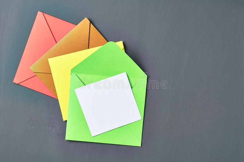 Blank white paper sheet near green opened square envelope lies on old scratched dark concrete. Space for text. Top view stock image