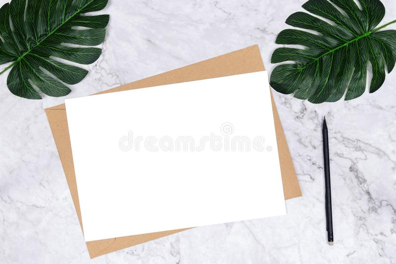Blank white paper size A4 on brown paper envelope on white marble background with green palm leaf on desk for decoration. Minimalist flat lay, top view royalty free stock image