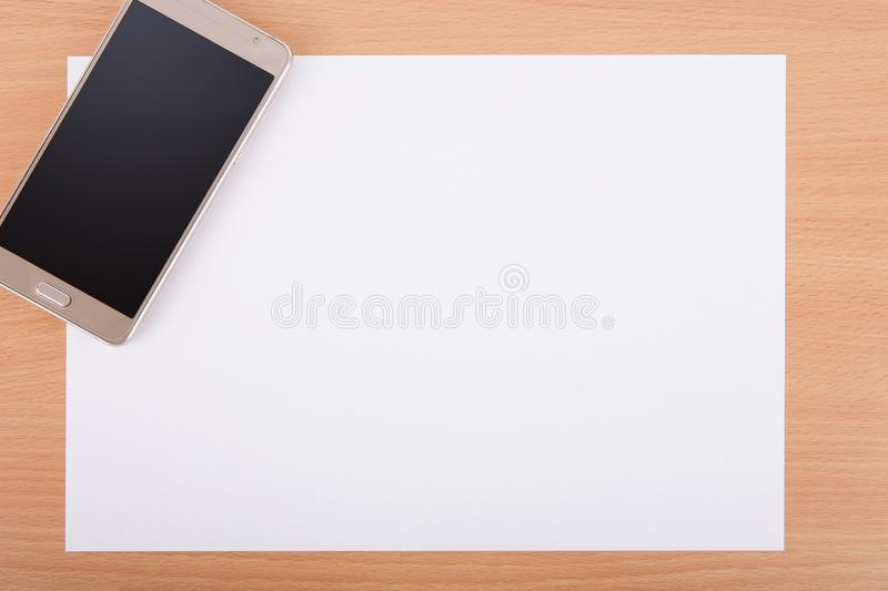 Blank A4 white paper with a smartphone on an office desk stock image