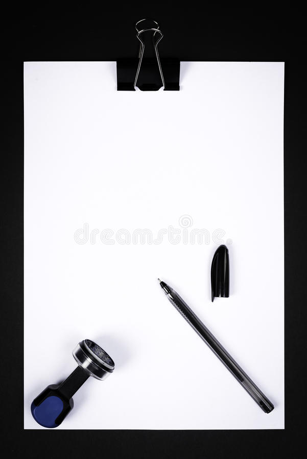 Blank white paper with stamp, ink pad and pencil. On black background stock photos