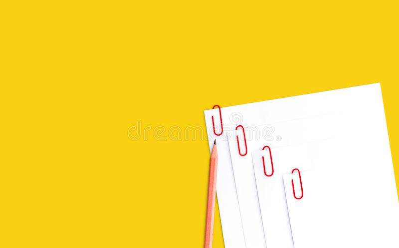 Blank white papers with red paper clips and pencil on yellow background with copy space for text or your image.  stock photo