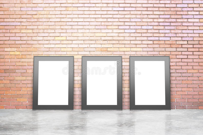 Blank white picture frames in empty loft room with concrete floor and red brick wall, mock up royalty free stock image