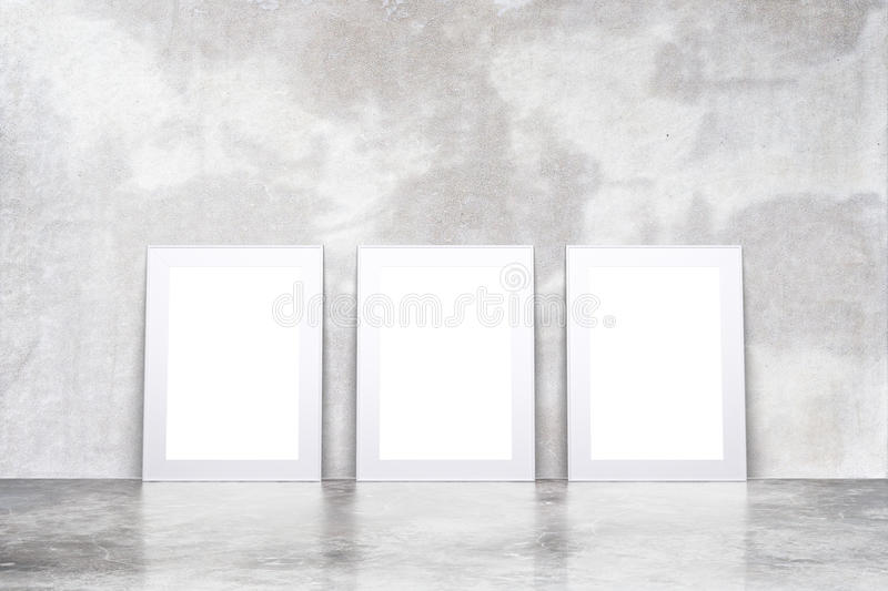 Blank white picture frames in empty loft room with concrete floor and wall, mock up stock images