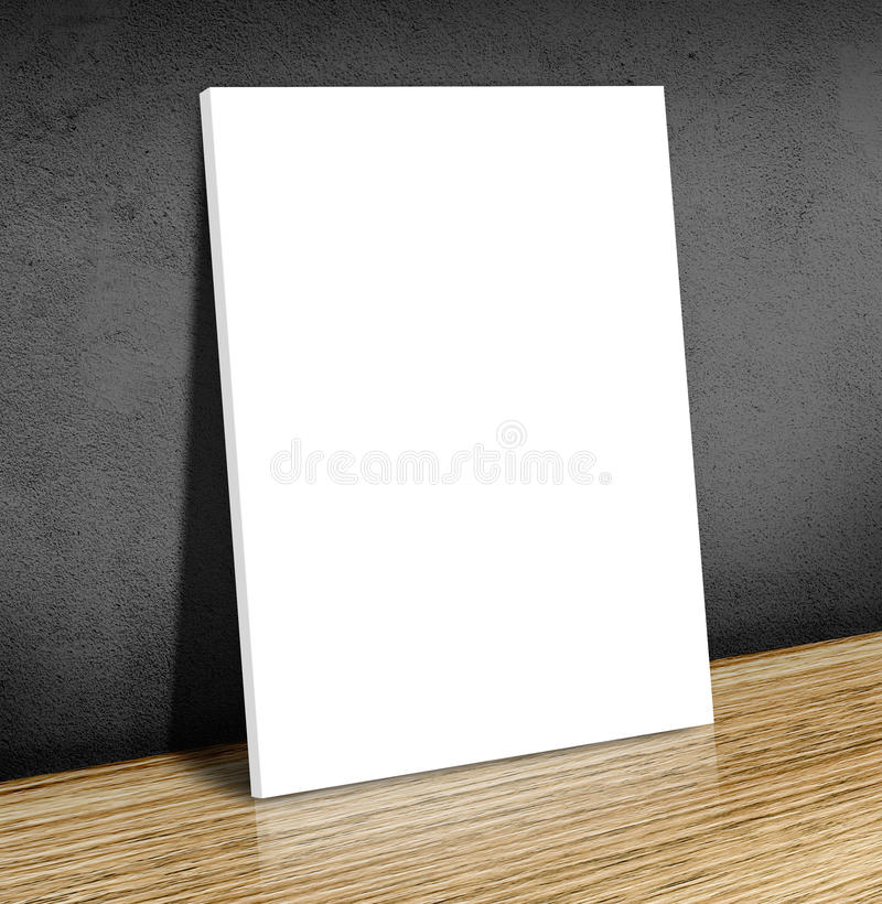 Blank white poster frame at wooden floor and black concrete wall. Canvas frame template mock up for adding your content,Business concept stock photography