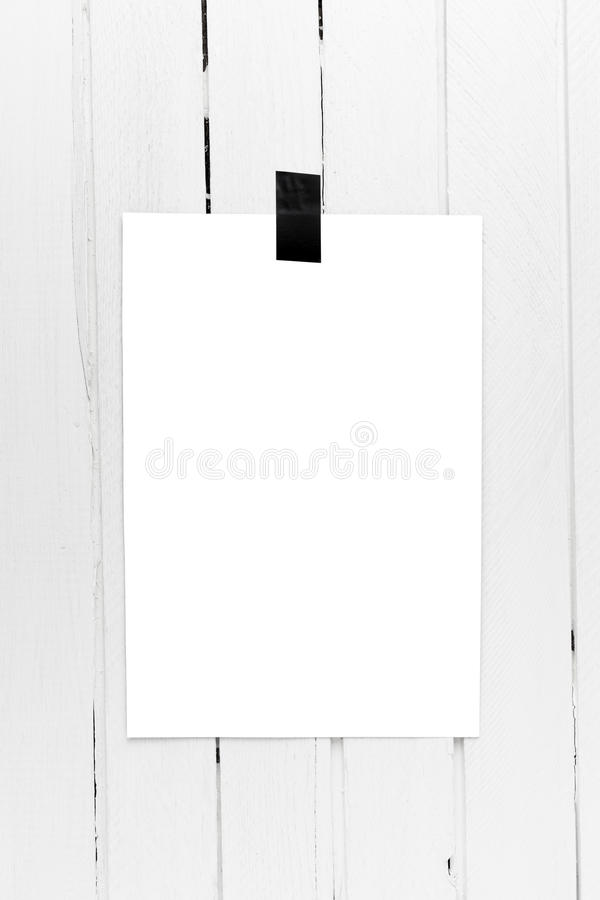 Blank white poster hanging on a tape on white wooden plank wall. Template background for your design royalty free stock images