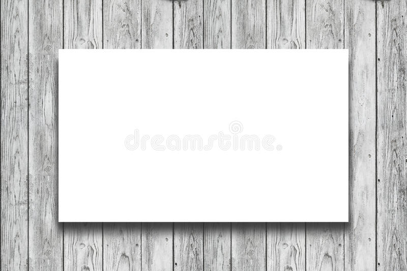 Blank white Poster. Hanging on wooden wall stock images