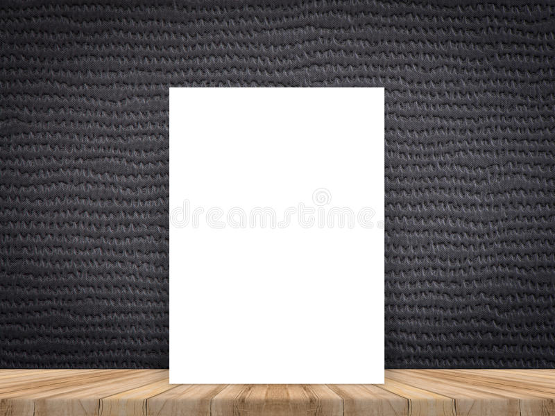 Blank white poster leaning at tropical wood table top with dark stock image