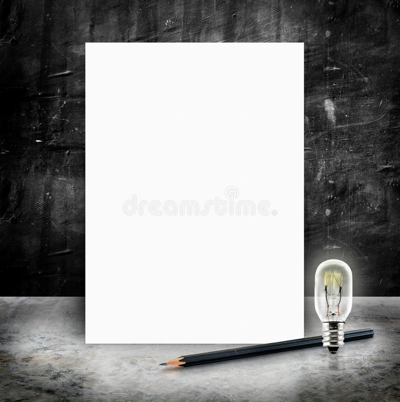Blank White poster with lightbulb and pencil in a glossy concrete floor and black grunge cement wall royalty free stock photos