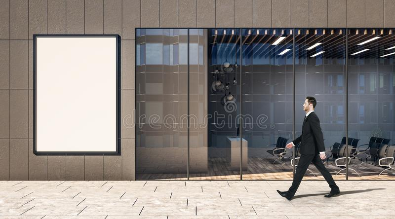 Blank white poster on a wall of business center and walking on a street businessman royalty free stock image