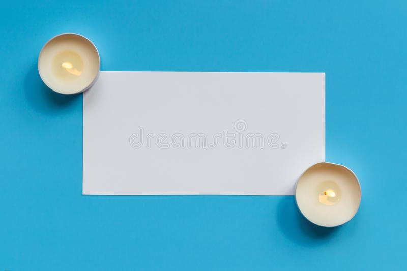 Blank white sheet of paper with burning candles on a blue background, top view. Mockup royalty free stock images