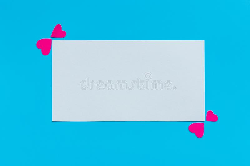 Blank white sheet of paper with pink hearts on a blue background, top view. Mockup stock photo