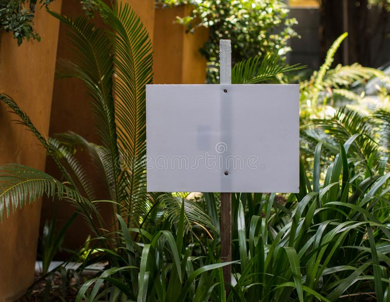 Blank white signboard in garden setting. Blank white signboard to insert own individual message on in a garden setting image in landscape format with copy space royalty free stock photo