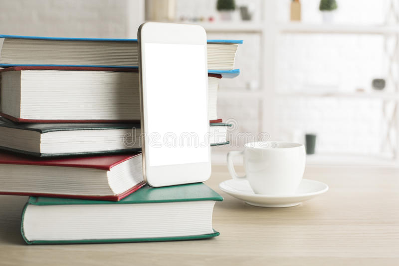 Blank white smartphone. Close up of blank white smartphone, pile of books and coffee cup on light wooden desktop. Mock up stock illustration