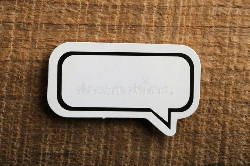 Blank White Speech Bubble Paper On Wooden Background stock image