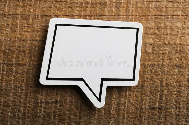 Blank White Speech Bubble Paper On Wooden Background stock photo